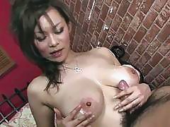 Busty Japanese strokes cock and sucks it like crazy